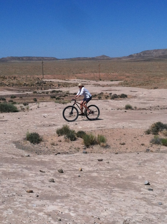 There are huge expanses of slick rock everywhere and no one riding it. Amelia couldn't hold back any longer. Here she is cruising my bike in flip flops and a straw hat.